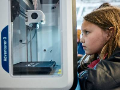 Photo of young girl watching a 3D printer