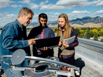 professor and two students on top of building examining computer and equipment with mountains in the background