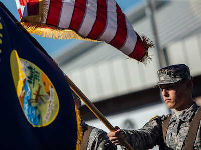 military ROTC student waving large Montana flag