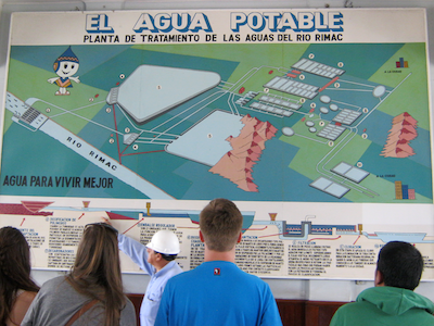 students in Peru looking at poster about water treatment