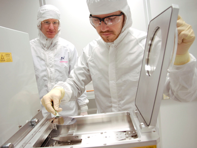 Student and professor in Montana Microfabrication Facility cleanroom wearing white cleansuits