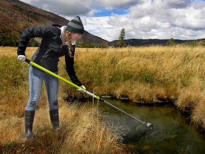 Student using pole to sample water from water body in Yellowstone Park, mountains in background