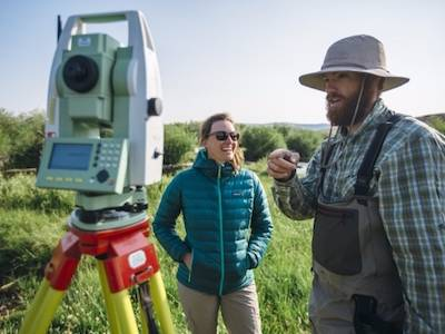 two MSU researchers in outdoors looking at surveying device