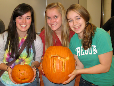 women students holding carved pumpkins at the Candyfest